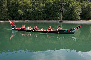 Many paddlers move a native canoe through the waters of Snug Cove