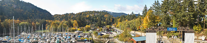 A panorama of the ferry dock, marina, trees and Cates Hill on Bowen Island, BC